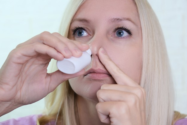 WOMAN WITH NASAL SPRAY